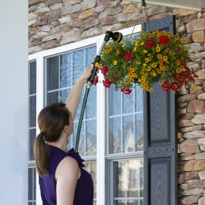 lady using watering wand to reach her hanging flower baskets